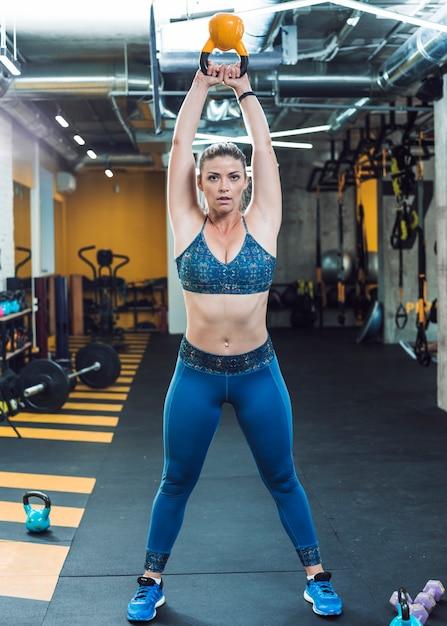 Retrato, de, um, ajuste, mulher, fazendo, exercício, com, chaleira, bola Foto gratuita