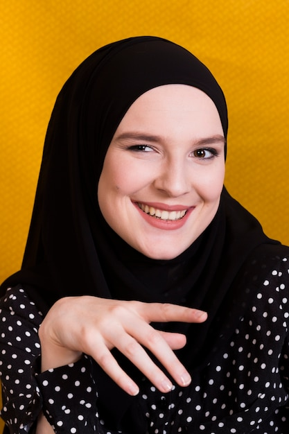 Retrato, de, um, alegre, islamic, mulher olha, câmera, contra, fundo amarelo Foto gratuita