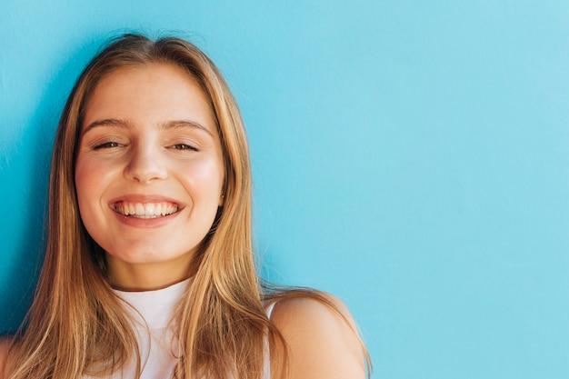 Retrato, de, um, alegre, mulher jovem, olhando câmera, contra, azul, fundo Foto gratuita