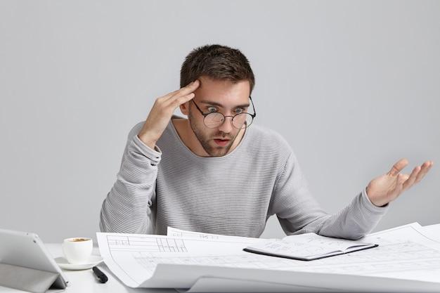 Retrato de um arquiteto ou designer masculino confuso, sentindo-se estressado, nervoso Foto gratuita