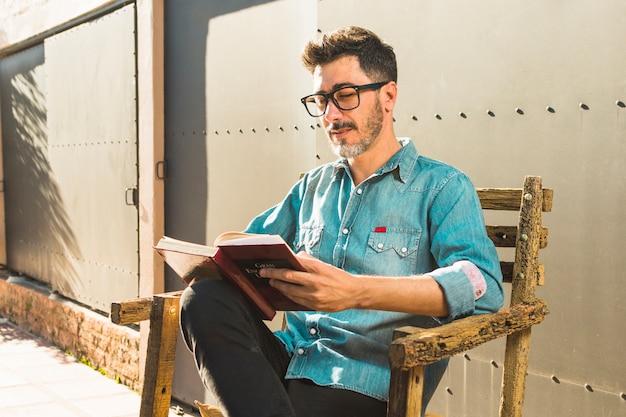 Retrato, de, um, assento homem, cadeira, lendo livro Foto gratuita
