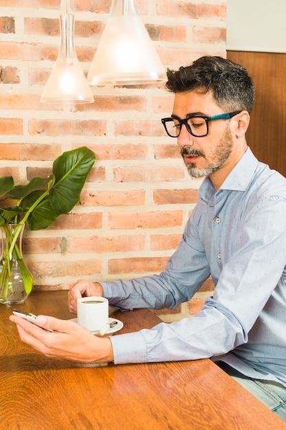 Retrato, de, um, assento homem, em, café, café bebendo, olhar telefone móvel Foto gratuita