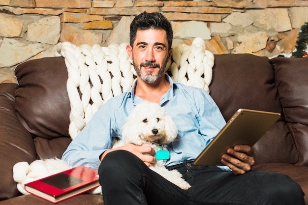 Retrato, de, um, assento homem, ligado, sofá, com, seu, cachorro branco, segurando, tablete digital, em, mão Foto gratuita