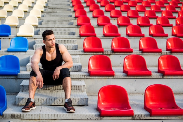Retrato de um atleta do sexo masculino sentado nos degraus da arquibancada de concreto Foto gratuita