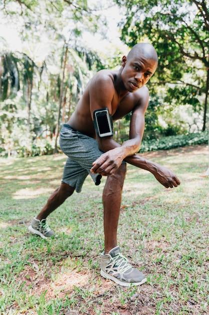 Retrato, de, um, atleta, homem jovem, em, a, parque, fazendo, esticar, exercícios Foto gratuita