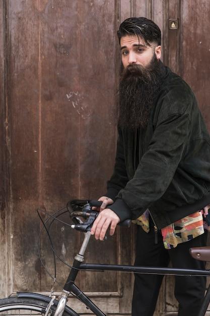 Retrato, de, um, bonito, homem jovem, com, longo, barba, ficar, com, seu, bicicleta Foto gratuita