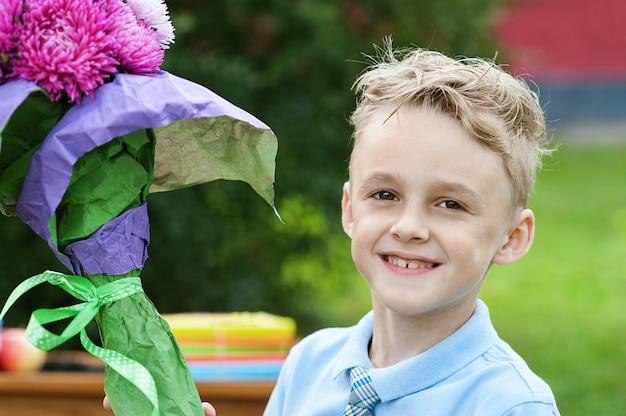 Retrato, de, um, bonito, jovem, first-grader, com, maçã vermelha, ligado, livros, em, um, uniforme escola festivo Foto Premium