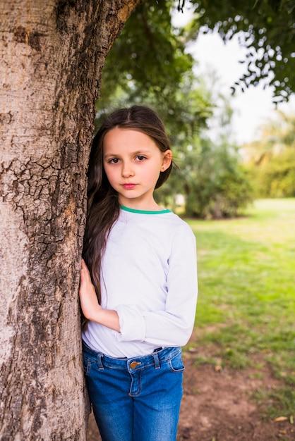 Retrato, de, um, bonito, menina, ficar, perto, tronco árvore, parque Foto gratuita