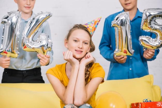 Retrato, de, um, bonito, menina sorridente, sentando, frente, meninos, segurando, numeral, 14, e, 15, folha, balões Foto gratuita