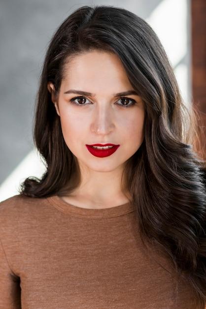 Retrato, de, um, bonito, mulher jovem, em, batom vermelho, olhando câmera Foto gratuita
