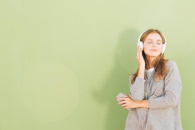 Retrato, de, um, bonito, mulher jovem, escutar música, ligado, auscultadores, através, telefone móvel, contra, hortelã, verde, fundo Foto gratuita