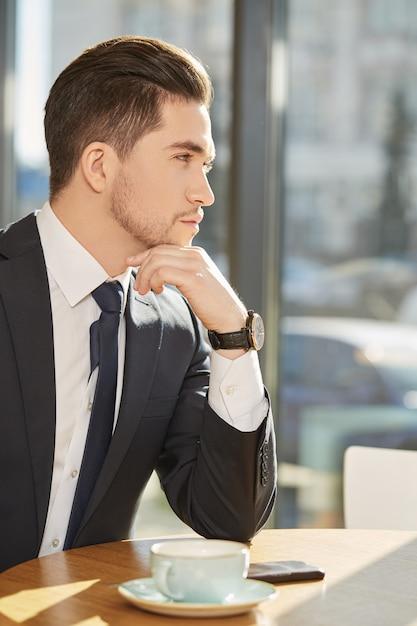 Retrato, de, um, bonito, sério, homem negócios, olhando, pensando, sobre, um, xícara café, em, a, café Foto Premium