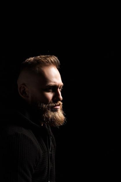 Retrato de um cara com barba no escuro Foto Premium
