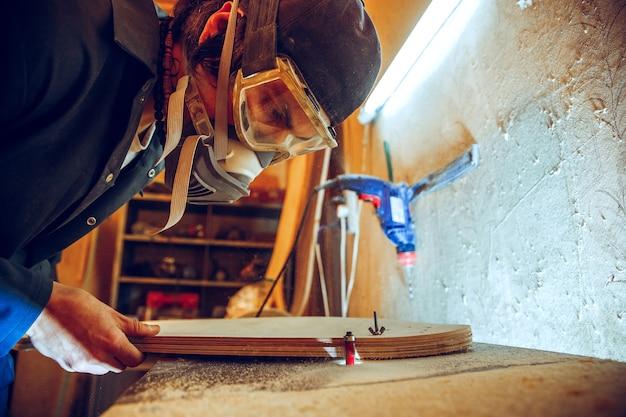 Retrato de um carpinteiro bonito trabalhando com um patim de madeira na oficina, vista de perfil Foto gratuita