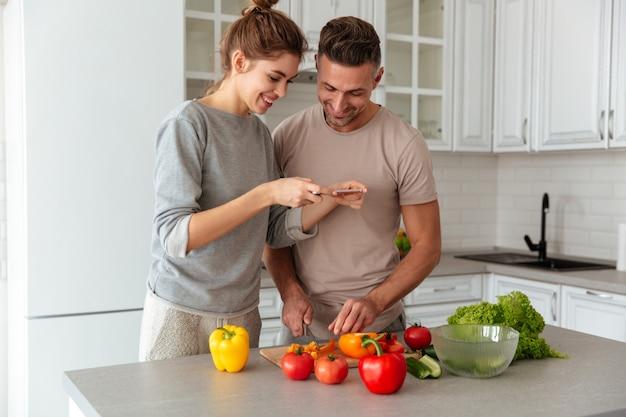Retrato de um casal amoroso feliz cozinhar salada juntos Foto gratuita