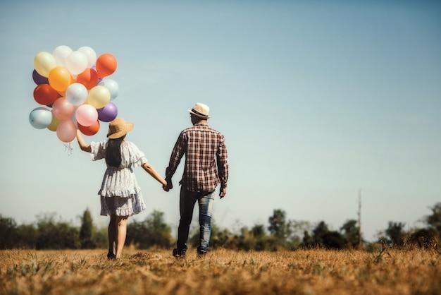 Retrato de um casal apaixonado andando com balões coloridos Foto gratuita