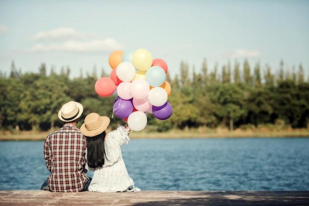 Retrato de um casal apaixonado por balões coloridos Foto gratuita