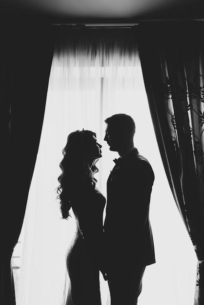 Retrato de um casal de silhueta romântica do noivo e noiva na janela Foto Premium