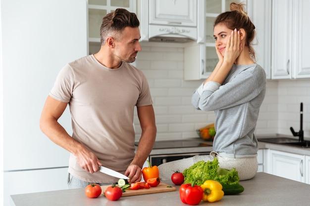Retrato de um casal muito amoroso cozinhar salada juntos Foto gratuita