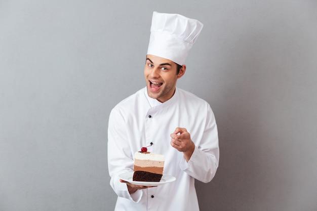 Retrato de um chef masculino alegre, vestido de uniforme Foto gratuita