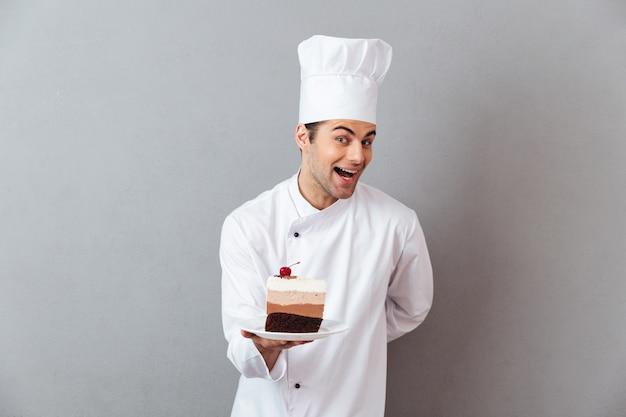 Retrato de um chef masculino animado sorridente, vestido de uniforme Foto gratuita