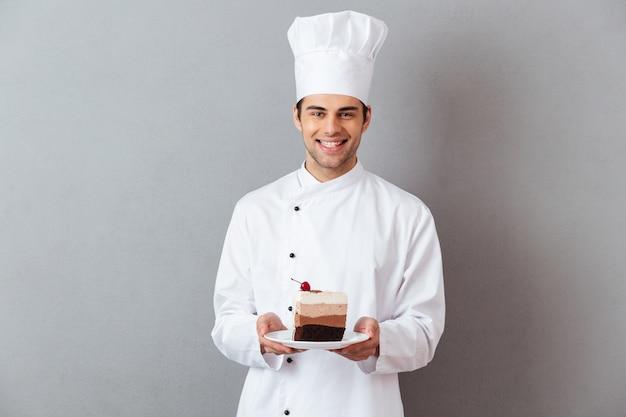 Retrato de um chef masculino feliz, vestido de uniforme Foto gratuita