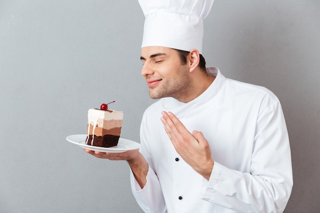 Retrato de um chef masculino satisfeito, vestido de uniforme Foto gratuita