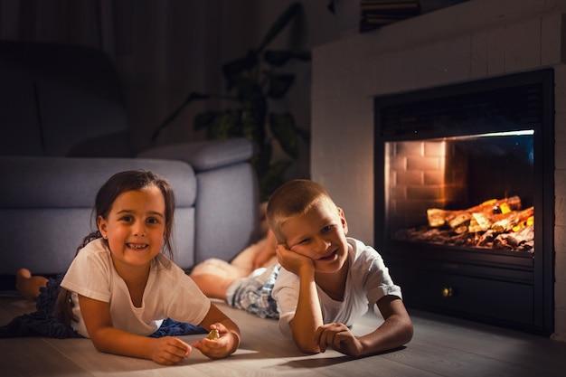 Retrato, de, um, childs, mentindo, frente, lareira Foto Premium