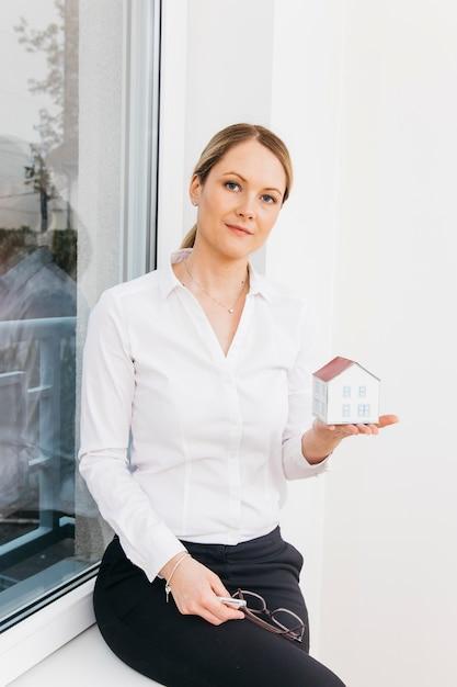 Retrato, de, um, confiante, mulher senta-se, selo janela, segurando, casa pequena, modelo Foto gratuita