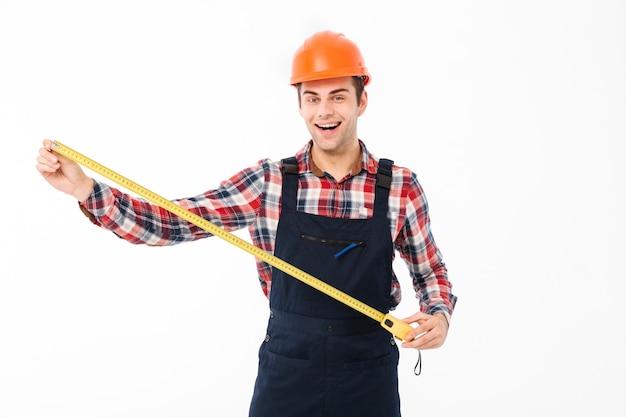 Retrato de um construtor masculino jovem feliz mostrando Foto gratuita