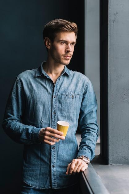 Retrato, de, um, contemplado, homem jovem, segurando, copo café descartável, em, mão Foto gratuita