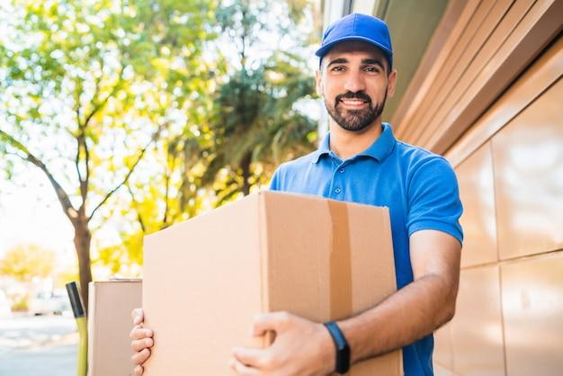 Retrato de um correio entregador com caixas de papelão nas mãos ao ar livre. entrega e conceito de envio. Foto Premium