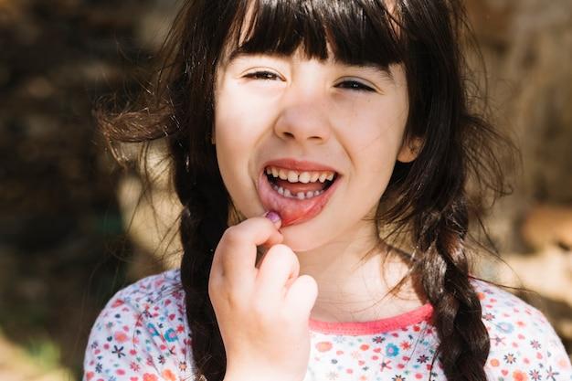 Retrato, de, um, cute, menininha, mostrando, dela, dentes quebrados Foto gratuita
