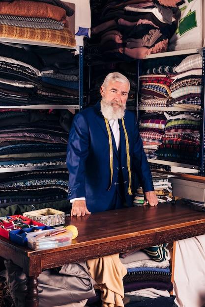 Retrato de um designer de moda masculina sênior em sua loja de roupas Foto gratuita