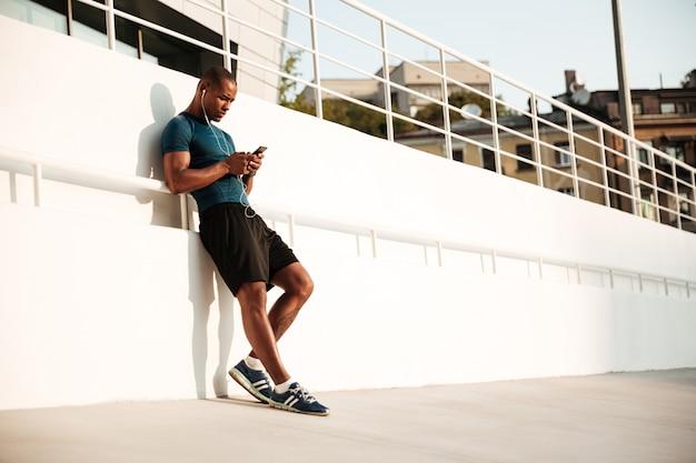 Retrato de um desportista afro-americana apto a ouvir música Foto gratuita