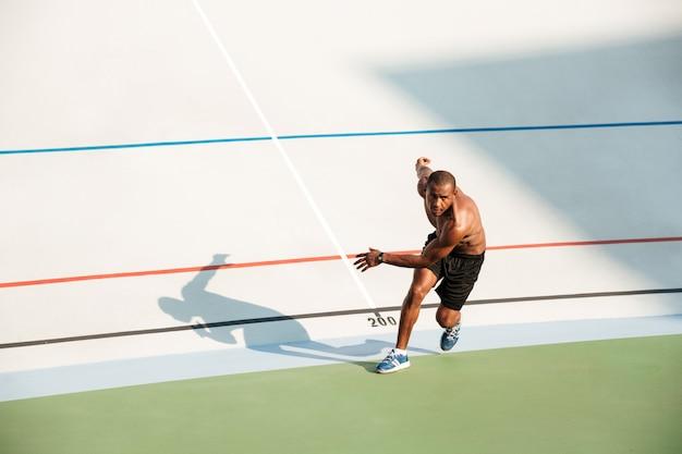 Retrato de um desportista saudável seminu começando a correr Foto gratuita