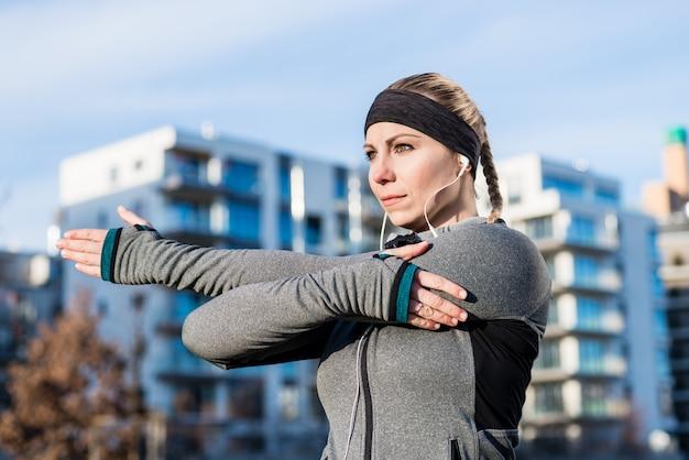 Retrato, de, um, determinado, mulher jovem, esticar, dela, braço esquerdo, dur Foto Premium