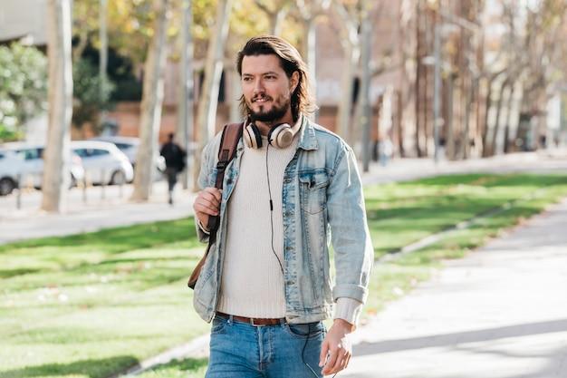 Retrato, de, um, elegante, homem jovem, com, headphone, ao redor, seu, pescoço, andar, parque Foto gratuita