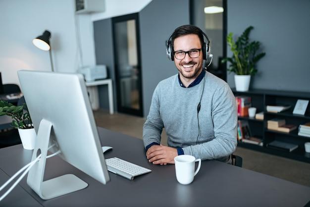 Retrato de um empregado masculino novo do centro de chamadas em seu escritório. Foto Premium