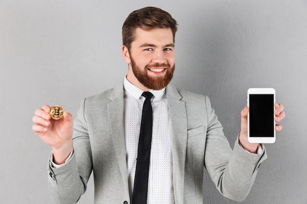 Retrato de um empresário alegre segurando bitcoin Foto gratuita