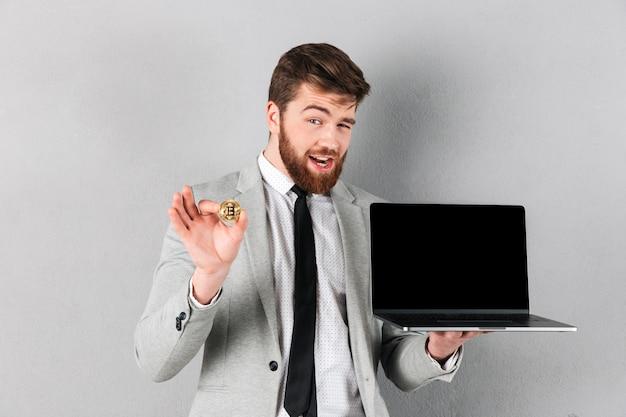 Retrato de um empresário bonitão segurando bitcoin Foto gratuita