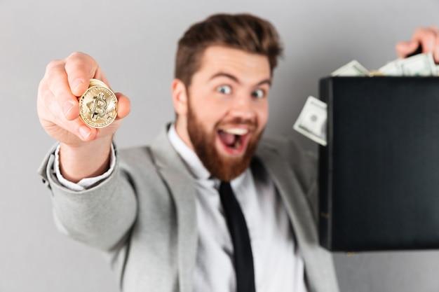 Retrato de um empresário confiante mostrando bitcoin dourado Foto gratuita