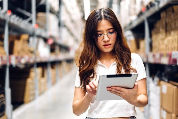 Retrato de um engenheiro asiático sorridente em detalhes de pedido de mulher de capacetes no computador tablet Foto Premium