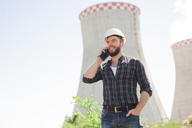 Retrato de um engenheiro bonito no trabalho com o telefone Foto Premium