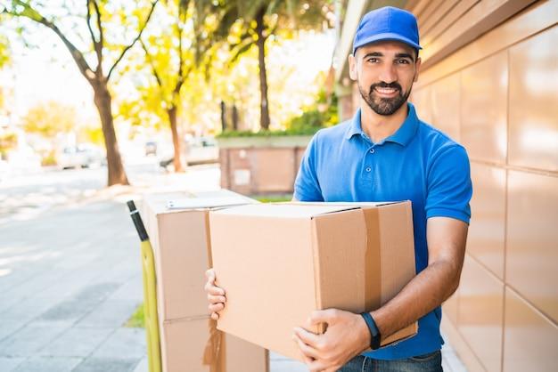 Retrato de um entregador com caixas de papelão nas mãos ao ar livre Foto Premium