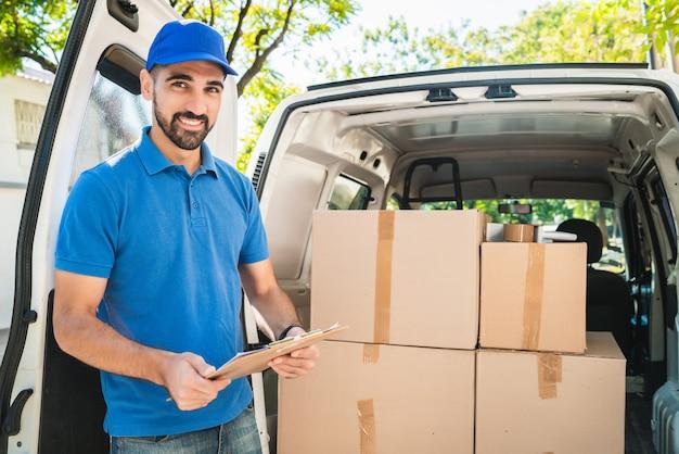 Retrato de um entregador verificando os produtos na lista de verificação ao lado de sua van. entrega e conceito de envio. Foto Premium