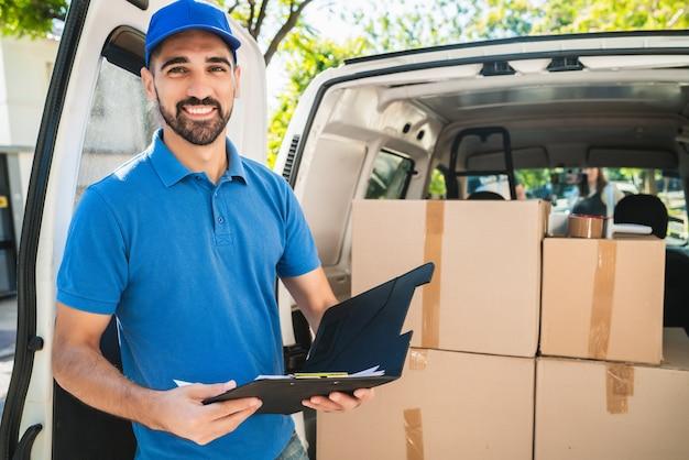 Retrato de um entregador verificando os produtos na lista de verificação ao lado de sua van Foto Premium