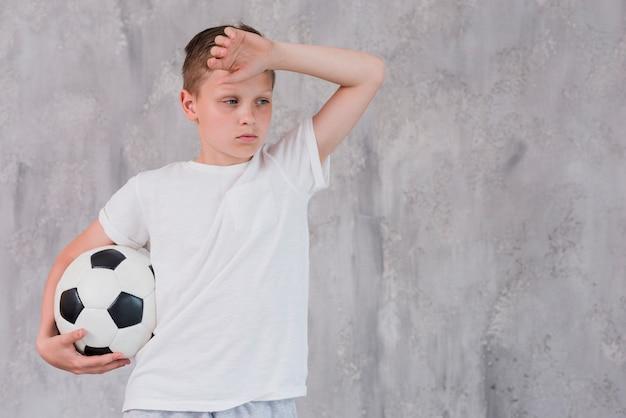 Retrato, de, um, esgotado, menino, segurando, bola futebol, em, mão, contra, parede concreta Foto gratuita