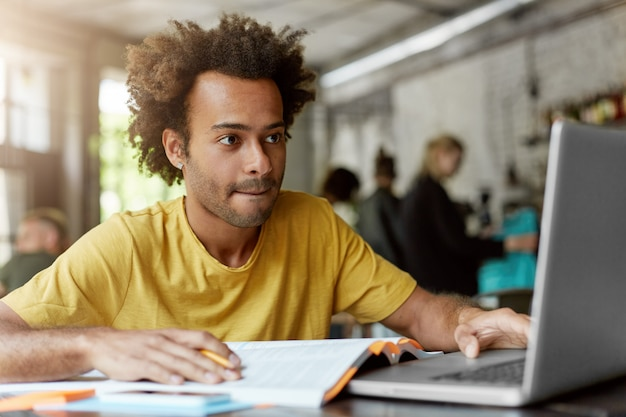 Retrato de um estudante inteligente com pele escura e cabelo espesso, vestindo roupas casuais, enquanto está sentado na lanchonete trabalhando em seu trabalho do curso em busca de informações na internet usando seu laptop Foto gratuita