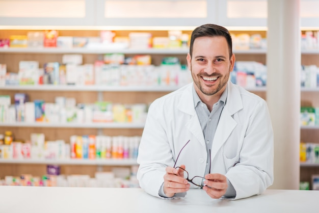 Retrato de um farmacêutico considerável alegre que inclina-se no contador na drograria. Foto Premium